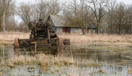 antique abandoned road grader in countryside (made in former USSR) against old barn photo