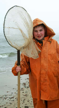 Young amber cather - fisherman smiling standing  by the sea with fisherman's coat on misty day Stock Photo - 5108449