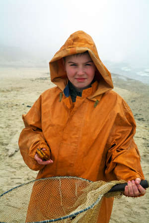 Young amber cather - fisherman smiling standing  by the sea with fishermans coat on misty day