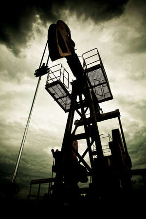 Oil rig pump dramaticly underexposed against contrast cloudy sky Standard-Bild