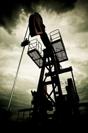 oilfield: Plataforma petrolera de la bomba dramaticly subexpuesta contra contraste cielo nublado
