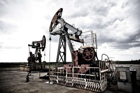yacimiento petrolero: Pums de petr�leo en los campos de contraste fr�o dando techno estado de �nimo en contra de Cloudscape dram�tica Foto de archivo