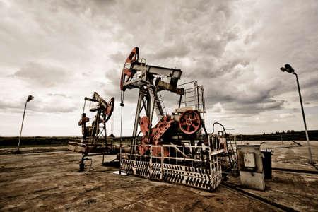 refiner�a de petr�leo: Pums de petr�leo en los campos de color oxidado vintage contra Cloudscape Moody