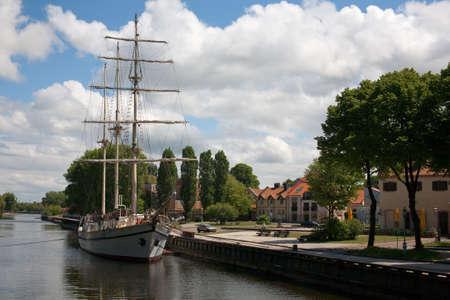 Sailboat moored at Klaip?da city center in the river Standard-Bild