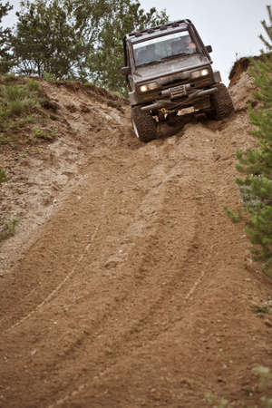 Closeup of 4x4 truck driving downhill trough mud