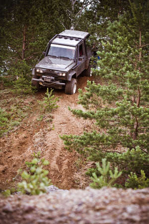 Closeup of 4x4 truck driving downhill  on the edge of hill