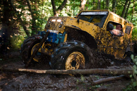 Pickup 4x4 truck driving trough mudy track in motion with sprays of mud