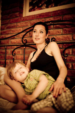 Young mother with her child son relaxing on the bed against brick wall background focus on  mother Stock Photo - 5585680