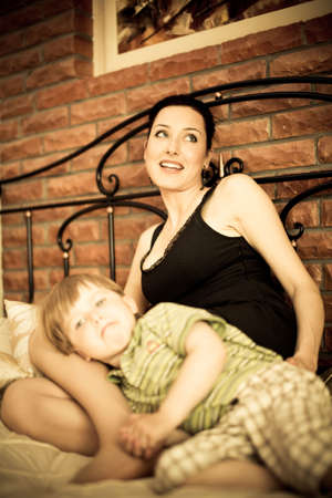 Young mother with her child son relaxing on the bed against brick wall background focus on mother photo