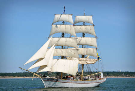 sailboat going out of port with full sails up