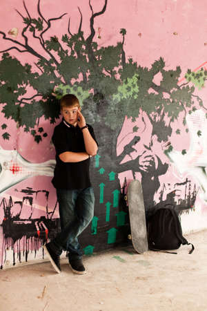 Young boy with shoulder bag and skateboard and graffiti wall in background