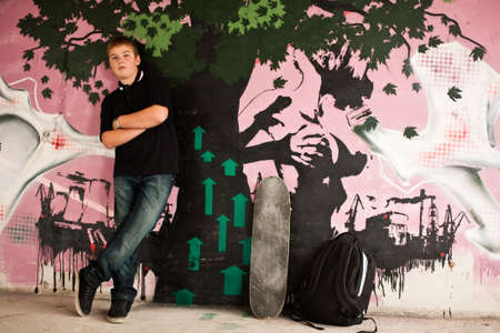 Teenage boy with skateboard against purple graffity wall check out more of the same series