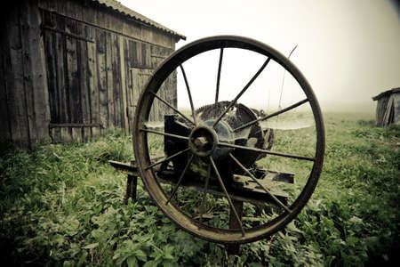 Vintage manual gras chopping machine in the misty autumn morning agaisnt barn, bleached colors photo