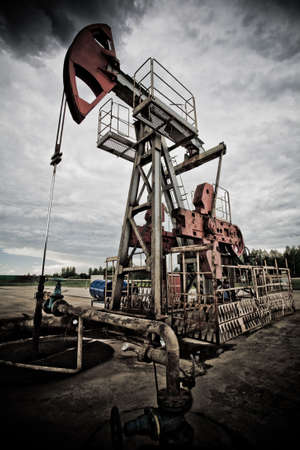 Oil rig pump dramaticly underexposed against contrast cloudy sky low angle view