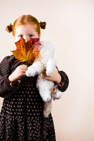 golden years series: Portrait of redhead girl over background with her favorite toy and maple leave