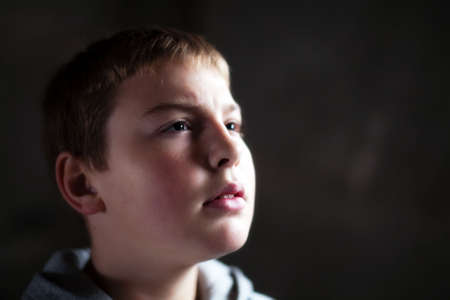 Young boy looking up with hope in his eyes against grunge background flash lit 3 light sources Stock Photo - 5979076