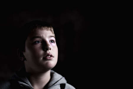 Young boy looking up with hope in his eyes against grunge background flash lit 3 light sources