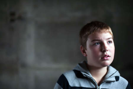 Young boy looking up with hope in his eyes against grunge background flash lit 3 light sources Stock Photo - 5979080