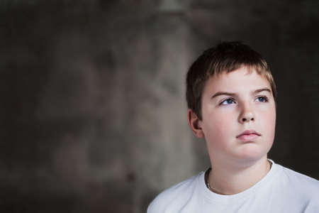 Young boy looking up with hope in his eyes against grunge background flash lit 3 light sources photo