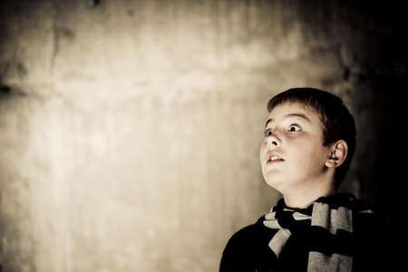 Young boy looking up with hope in his eyes against grunge background flash lit 3 light sources Stock Photo - 5979077
