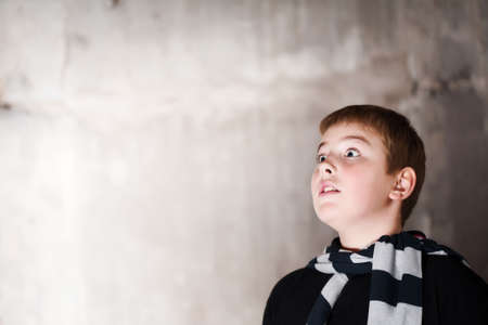 Young boy looking up with hope in his eyes against grunge background flash lit 3 light sources Stock Photo - 5979061