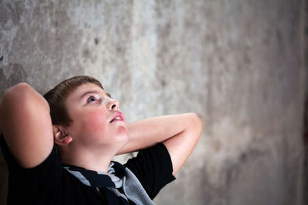 captivated: Young boy looking up with hope in his eyes against grunge background flash lit 3 light sources