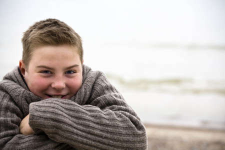 Teenager boy looking at camera in cold weather with sveater look for more o the same model photo