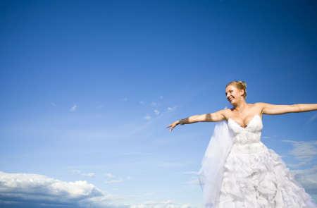 Happy bride aggainst  background of blue sky Фото со стока