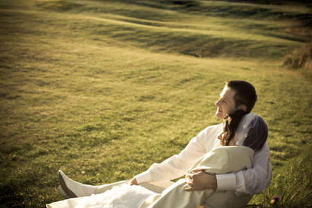 Bride and groom on the grass looking at sunset and last rays of evening sun