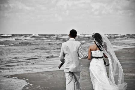 happy wedding couple walking along seashore desaturated