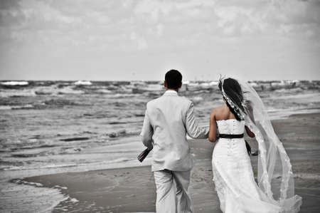 happy wedding couple walking along seashore desaturated