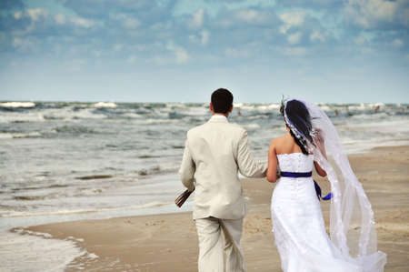 woman beach dress: happy wedding couple walking along seashore Stock Photo