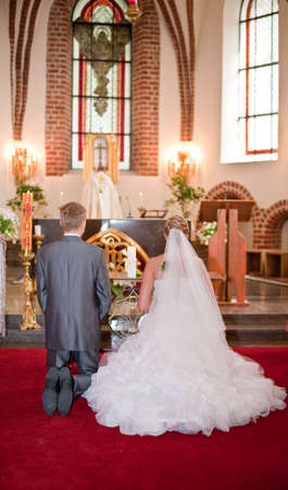 christian altar: Bride and groom kneeling on wedding ceremony in front of altar
