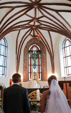 Bride and groom kneeling on wedding ceremony in front of altar photo