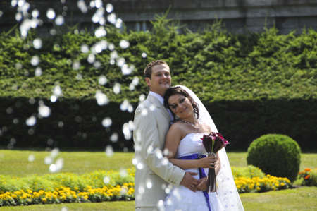 Groom and bride in public park with fontain sprais photo