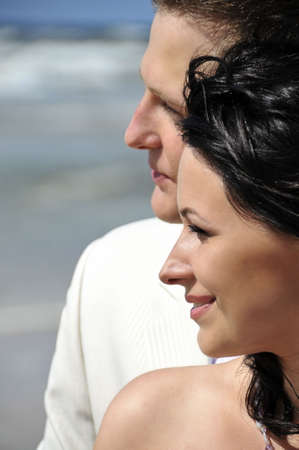 happy wedding couple portrait along seashore looking forward photo