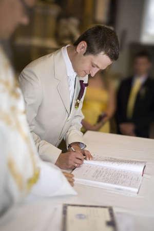The wedding signature. Groom signing the register Standard-Bild