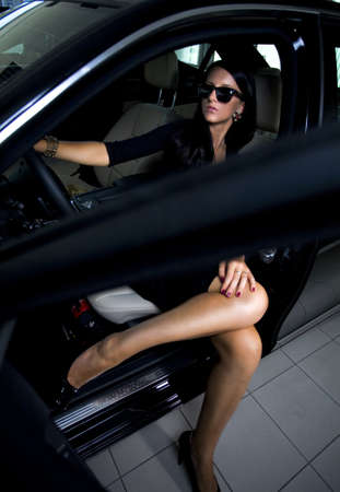 Sexy woman in luxury car with long legs photo