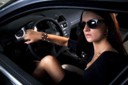 Sexy elegant woman in luxury car with long legs