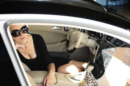 Sexy woman in luxury car thinking legs