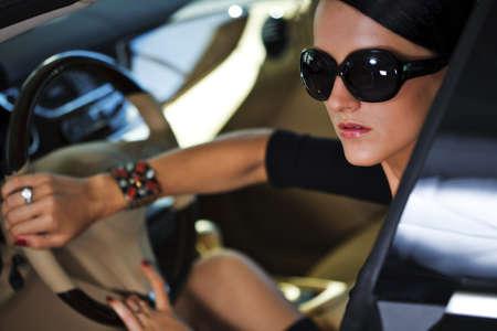 Sexy woman sitting in luxury car  Standard-Bild