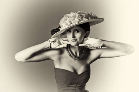 Young woman isolated on gray vintage hat and syle black and white Фото со стока