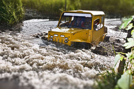 4x4 truck driving trough mudy track in motion with sprays of mud photo