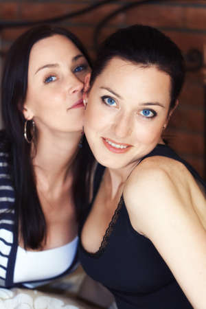 Two elegant sexy sisters looking at camera photo