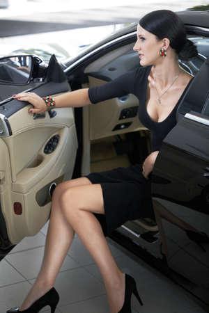 Femme sexy dans la voiture de luxe avec de longues jambes photo
