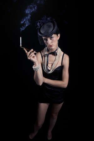 Woman with cigarette and vintage hat with long legs against dar background photo