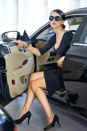 Sexy woman in luxury car with long legs