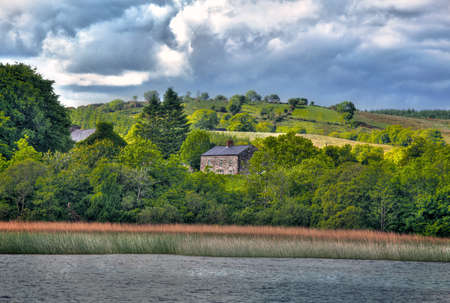 View to Irish cottage from boat river Shanon