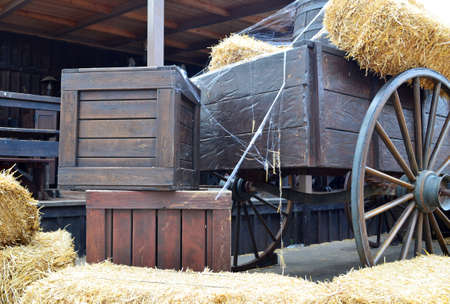 old wood farm wagon: Old cart and wooden boxes in a barn Stock Photo