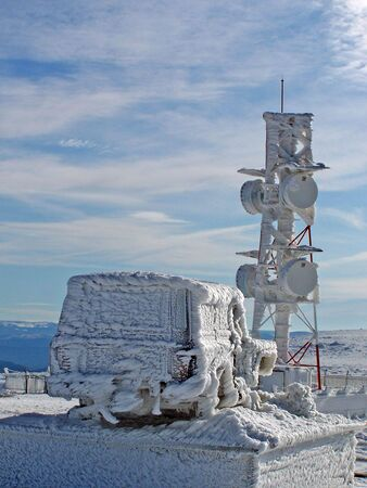 meteo: A meteo observatory and a car covered with frozen snow, looking like scupltures